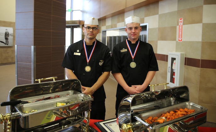 Sgt. Hugo P. Zepeda and Lance Cpl. Justin Gordon, food service specialists with Headquarters Squadron, Marine Corps Air Station Yuma, pose for a photograph after taking first place honors at the MCI-West Chef of the Quarter culinary competition here, Dec. 3.  The two were awarded medals and priority seats for a two-month course at the Culinary Institute of America