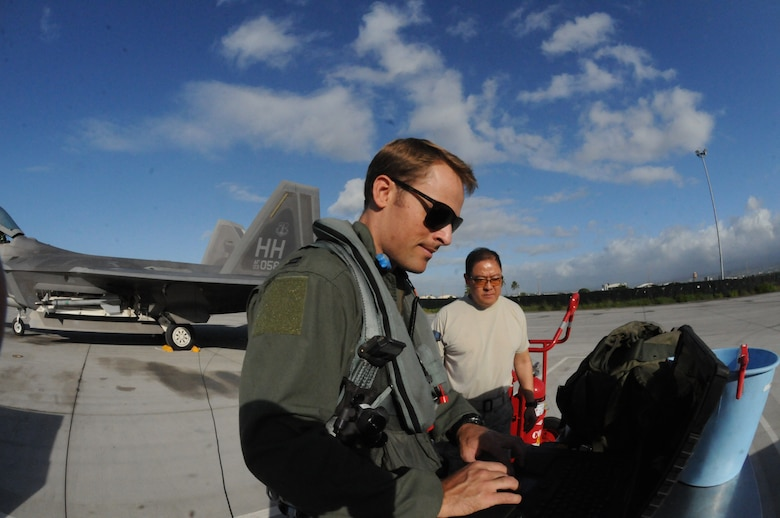 Capt. Austin McIntosh,19th Fighter Squadron F-22 pilot, and Tech. Sgt. Jay Nishimura, 154th Aircraft Maintenance Squadron Avionic Systems specialist, review aircraft forms  prior to taking-off from Joint Base Pearl Harbor Hickam, Hawaii Nov. 20. Airmen from the 15th and 154th Wings exercised the Rapid Raptor concept, the newest approach to fighter employment, which uses at least one C-17 to swiftly move, refuel and rearm a minimum of four F-22s in unfamiliar environments.(Hawaii Air National Guard photo/Senior Airman Orlando Corpuz)