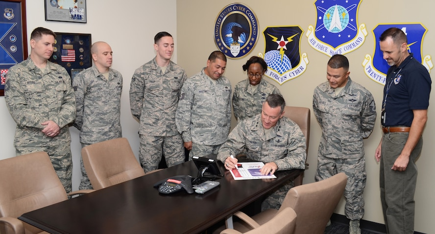 Combined Federal Campaign representatives from across 24th Air Force headquarters look on while Maj. Gen. B. Edwin Wilson (seated), 24th AF commander, updates the CFC contribution chart.  Also pictured are (standing, from left to right), Tech. Sgt. Michael Ayers, Staff Sgt. Matthew Gibson, Senior Airman Jonathan Troup, Tech. Sgt. Salvador Martinez, Master Sgt. Tiffany Gatling, Master Sgt. Mark Mendez, and Jonathan Blount.  (U.S. Air Force photo by Senior Master Sgt. Dorian Chapman)