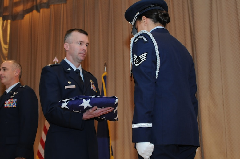 """Col. Jeremy """"Weed"""" Baenen accepts a flag in honor of his 26 years of service to the United States Air Force and the Oregon Air National Guard during his retirement ceremony, Nov. 21, 2014 at Kingsley Field in Klamath Falls, Ore. The day marked his last as the 173rd Fighter Wing Commander. (U.S. Air National Guard photo by Tech. Sgt. Jefferson Thompson/Released)"""