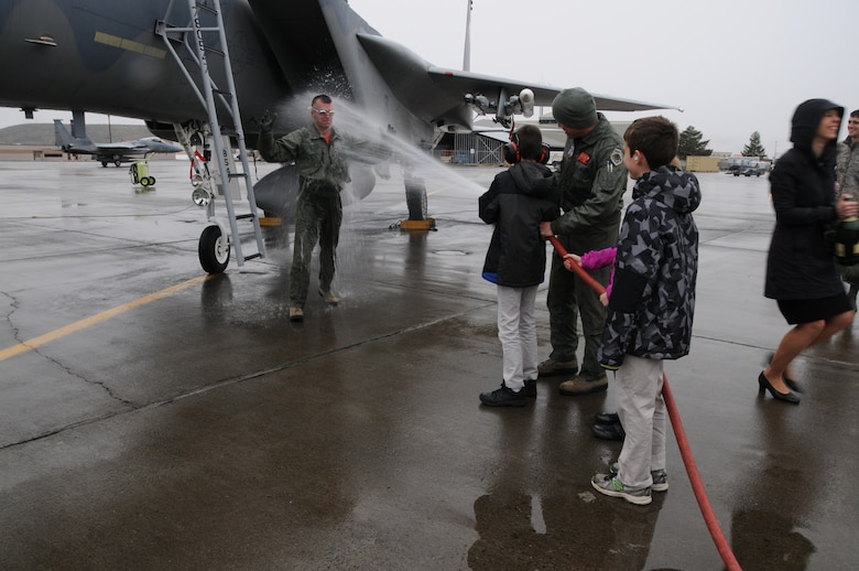 """Col. Jeremy """"Weed"""" Baenen welcomes a cold blast of water upon stepping to the tarmac following his last flight in the F-15 Eagle shortly before his retirement ceremony, Nov. 21, 2014. The dousing is part of the traditional fini flight for pilots upon their last flight in an aircraft. (U.S. Air National Guard photo by Tech. Sgt. Jefferson Thompson/Released)"""