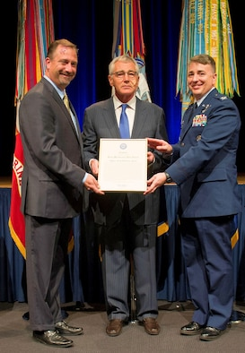 Col. John Cinnamon (right), the 71st Operations Group commander, and Ken Myers (left), the Defense Threat Reduction Agency director, accept a Joint Meritorious Unit Award from Secretary of Defense Chuck Hagel, during a ceremony at the Pentagon Nov. 12. Cinnamon was the chief of plans for DTRA from June 2012 to June 2014 before he joined Team Vance.  (U.S. Air Force photo/MSgt. Adrian Cadiz)