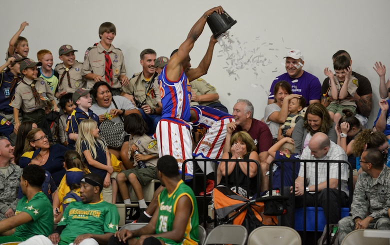Hi-Lite, from The Harlem Globetrotters, dumps a bucket of paper onto the fans, Dec. 1, 2014, at Andersen Air Force Base, Guam. The Globetrotters captivated Team Andersen with their athleticism, theater and comedy as well as its audience participation, choreography, tricks and their overall basketball skill. (U.S. Air Force photo by Staff Sgt. Robert Hicks/Released)