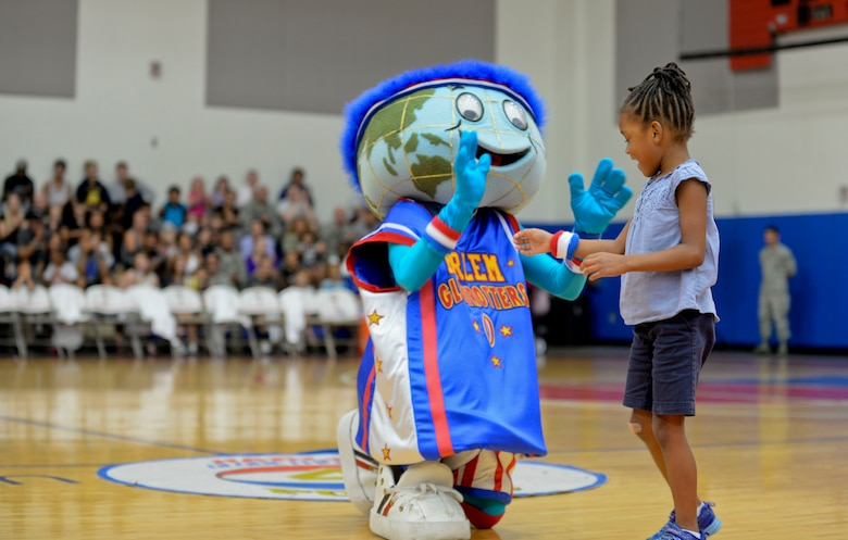 Globie, the Harlem Globetrotter mascot, gives a wristband to a Team Andersen member after winning a game of musical chairs, Dec. 1, 2014, at Andersen Air Force Base, Guam. The Globetrotters captivated Team Andersen with their athleticism, theater and comedy as well as its audience participation, choreography, tricks and their overall basketball skill. (U.S. Air Force photo by Staff Sgt. Robert Hicks/Released)
