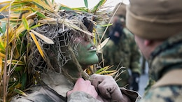 U.S. Marine Lance Cpl. Jonas G. Dewald works with a fellow Marine to don his ghillie suit Dec. 2 in the Oyanohara Training Area in Yamato, Kumamoto prefecture, Japan. The concealment training is part of Forest Light 15-1, a semi-annual, bilateral exercise consisting of a command post exercise and field training events conducted by elements of III Marine Expeditionary Force and the Japan Ground Self-Defense Force to enhance the U.S. and Japan military partnership, solidify regional security agreements and improve individual and unit-level skills. Dewald, from Wilson, North Carolina, is a machine gunner with Weapons Company, 2nd Battalion, 9th Marine Regiment, currently attached to 4th Marine Regiment, 3rd Marine Division, III MEF, under the unit deployment program. (U.S. Marine Corps photo by Cpl. Drew Tech/Released)