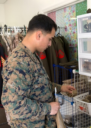 Lance Cpl. Erick Ramirez, an aviation electrician with Marine Aviation Logistics Squadron 26, looks at free uniform items at Ramblin' Rose Thrift Shop aboard Marine Corps Air Station New River, Nov. 20. All military uniforms and accessories are free to active-duty service members at the thrift shop.