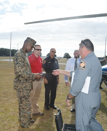 Marine Corps Logistics Base officials inspect a piece of equipment during a pre-training exercise with Georgia State Patrol Aviation pilot, Wayne Wiley, recently. The equipment will allow emergency management staff to monitor ground activity downloaded by GSP AD pilots in the event of an on-base incident.