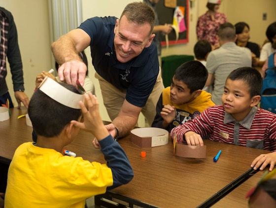 Col. Ronald Braney, from Stafford, Virginia, places an American Indian hat on a child's head Nov. 23 during the second annual Thanksgiving celebration with Tai Chu En Children's Home at the Camp Kinser Chapel. The event began with the children assembling paper hats as the Marines, sailors and spouses assisted them. Following the crafts, the children and volunteers sat down for a Thanksgiving feast including turkey, corn and pumpkin pie. Braney is the commanding officer for Combat Logistics Regiment 35, 3rd Marine Logistics Group, III Marine Expeditionary Force.