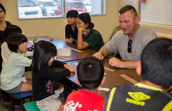 Gunnery Sgt. Shane R. Bertrand, from Ontario, Oregon, helps children put together paper pilgrim and American Indian hats Nov. 23 during the second annual Thanksgiving celebration with Tai Chu En Children's Home at the Camp Kinser Chapel. This was the second annual Thanksgiving event with the children's home and the Marines and sailors with Combat Logistics Regiment 35. Following the crafts, the children and volunteers sat down for a Thanksgiving feast including turkey, corn and pumpkin pie. Bertrand is the logistics chief for CLR 35, 3rd Marine Logistics Group, III Marine Expeditionary.