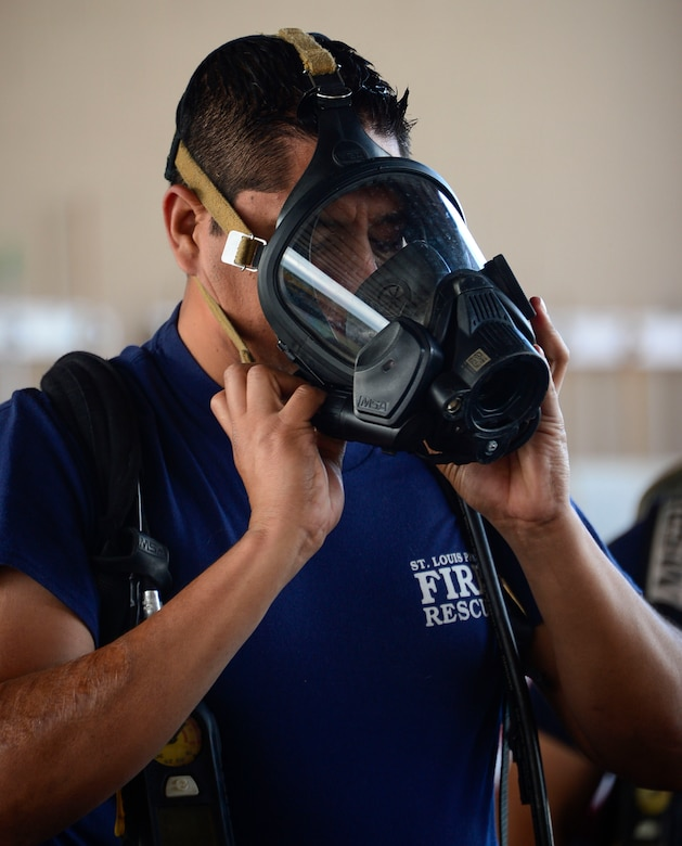 A firefighter from El Salvador tries on a breathing mask during the self-contained breathing apparatus orientation given by the 612th Air Base Squadron firefighters during El Salvador's Autonomous Executive Port Commission airport firefighter live-fires on Soto Cano Air Base, Honduras, Dec. 3, 2014.  The 612th ABS firefighters facilitated El Salvador's Executive Port Commission airport firefighter qualification by providing live-fires.  The Salvadoran airport firefighters have a requirement very similar to the United States standards that requires members of their airport fire departments to be qualified annually on their ability to control a live-fire.  (U.S. Air Force photo/Tech. Sgt. Heather Redman)