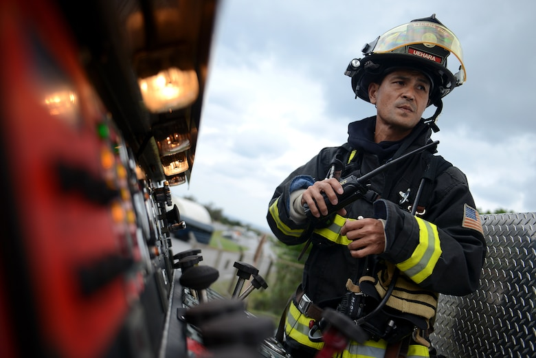 Keira Uehara listens to the radio atop a fire truck during a simulated hazardous materials vehicle crash as part of a mission focused exercise Dec. 2, 2014, on Kadena Air Base, Japan. The exercise tested Airmen on their ability to survive and operate in a multitude of stressful environments. Uhara is a 18th Civil Engineer Squadron firefighter. (U.S. Air Force photo/Senior Airman Maeson L. Elleman)