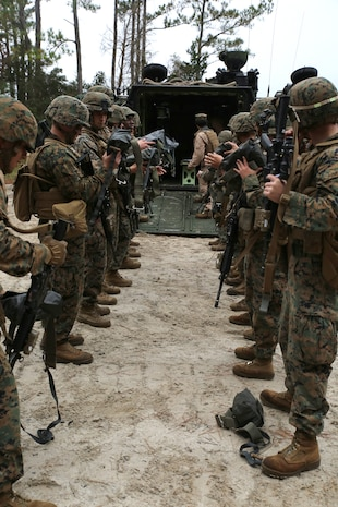 Marines with 3rd Platoon, Company A, Ground Combat Element Integrated Task Force, prepare to don life vests before boarding amphibious assault vehicles at Marine Corps Base Camp Lejeune, North Carolina, Dec. 2, 2014. Marines with AAV Platoon, Company B, GCEITF, transported Co. A Marines to the Verona Loop training area on Camp Lejeune to conduct a three-day live fire event with the M27 Infantry Automatic Rifle. (U.S. Marine Corps photo by Sgt. Alicia R. Leaders/Released)