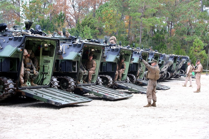 Marines with the Amphibious Assault Vehicle Platoon, Company B, Ground Combat Element Integrated Task Force, supervise the closing of the ramps on the AAVs in preparation to depart the French Creek loading dock at Marine Corps Base Camp Lejeune, North Carolina, Dec. 2, 2014. Marines with AAV Platoon, Company B, GCEITF, transported Co. A Marines to the Verona Loop training area on Camp Lejeune to conduct a three-day live-fire training event with the M27 Infantry Automatic Rifle. (U.S. Marine Corps photo by Sgt. Alicia R. Leaders/Released)