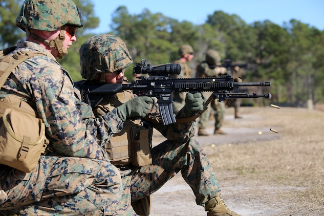 Cpl. Joshua T. Long, rifleman and position safety officer, 2nd Platoon, Company A, Ground Combat Element Integrated Task Force, observes as Sgt. Margarita B. Valenzuela, rifleman with 1st Platoon, Company A, , engages known-distance targets with the M27 Infantry Automatic Rifle from the kneeling position during a three-day field exercise at the Verona Loop training area on Marine Corps Base Camp Lejeune, North Carolina, Dec. 3, 2014. (U.S. Marine Corps photo by Sgt. Alicia R. Leaders/Released)