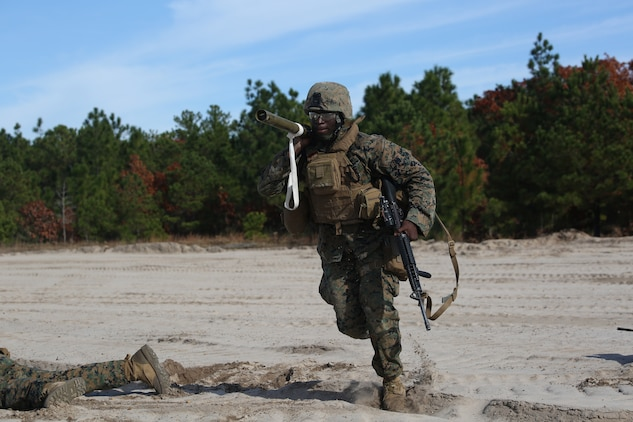 Lance Cpl. Amadu Kanu, combat engineer with Engineer Platoon, Headquarters and Service Company, Ground Combat Element Integrated Task Force, advances to an objective with an M1A2 Bangalore torpedo during an assault breaching exercise at Engineer Training Area 2 at Marine Corps Base Camp Lejeune, North Carolina,  Dec. 3, 2014. (U.S. Marine Corps photo by Cpl. Paul S. Martinez/Released)