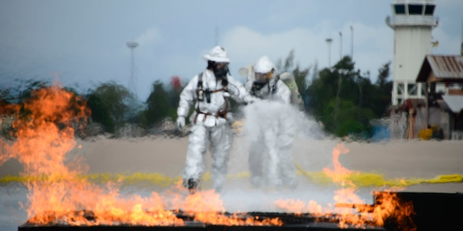Firefighters from El Salvador start to extinguish a simulated petroleum, oil, and lubricants running pool fire during the El Salvador's Autonomous Executive Port Commission airport firefighter live fires Dec. 3, 2014, on Soto Cano Air Base, Honduras. The 612th Air Base Squadron firefighters facilitated El Salvador's Autonomous Executive Port Commission airport firefighter qualification by providing live fires. The Salvadoran airport firefighters have a requirement very similar to the United States standards that requires members of their airport fire departments to be qualified annually on their ability to control a live fire. (U.S. Air Force photo/Tech. Sgt. Heather Redman)