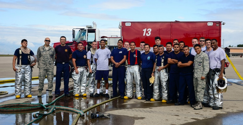 Firefighters from the 612th Air Base Squadron and El Salvador gather together after El Salvador's Autonomous Executive Port Commission airport firefighter live fires Dec. 3, 2014, on Soto Cano Air Base, Honduras. The 612th ABS firefighters facilitated El Salvador's Autonomous Executive Port Commission airport firefighter qualification by providing live fires. The Salvadoran airport firefighters have a requirement very similar to the United States standards that requires members of their airport fire departments to be qualified annually on their ability to control a live fire. (U.S. Air Force photo/Tech. Sgt. Heather Redman)