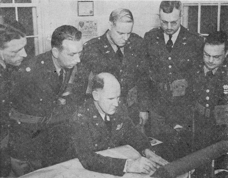 Col Stromme, Commander of Portland AAB, seated, and his staff read the declaration of war after the Japanese attack in the Pacific.  Standing behind him, left to right, are Captain Herbert S. Beeks, Commander, 43rd ABG, Major Milton W. Kingcaid, base executive officer, Major Glen G. Heavenridge, Commander, HQ and HQ Squadron, Captain Walter W. Robinson, Base S-1 and Captain Alexander Cohn, Supply Officer.  Note the standing officers in service dress uniforms, with M-1936 pistol belts and .45 caliber automatic pistol ammunition pouches.  (142FW History Archives)
