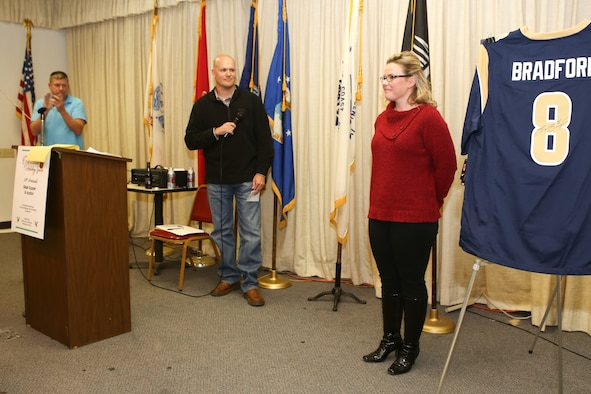 Staff Sgt. Ashley Osborn, right, a flight medic with the 137th Aeromedical Evacuation Squadron, receives a standing ovation on November 1 after sharing her story at the 16th annual Operation Holiday Spirit fundraiser at the Del City American Legion. Osborn received support from the organization three years ago when her son was hospitalized and diagnosed with meningitis. (U.S. Air Force photo/Staff Sgt. Caleb Wanzer)