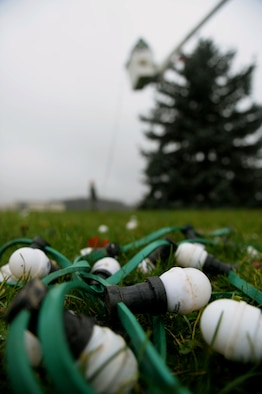 Decoration lights rest on the grass in front of an evergreen tree at the Saber Circle in Spangdahlem Air Base, Germany, Dec. 2, 2014. Airmen used multi-colored lights and cords to decorate the tree. (U.S. Air Force photo by Airman 1st Class Timothy Kim/Released)