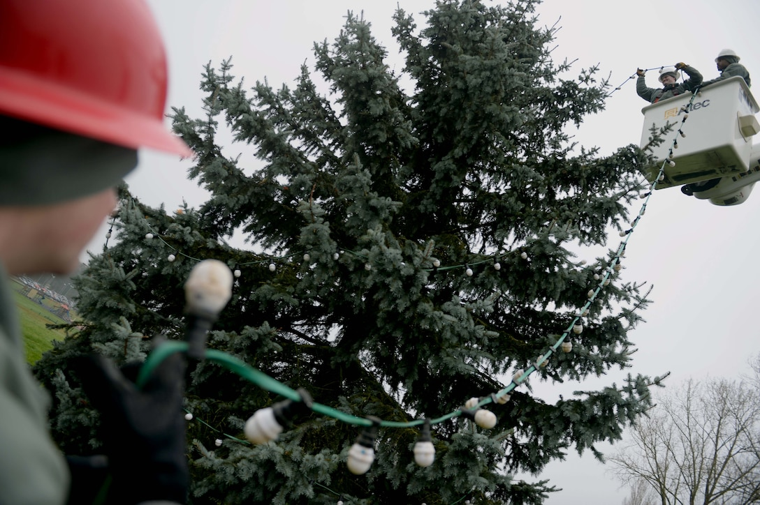 U.S. Air Force Airmen from the 52nd Civil Engineer Squadron Airmen decorate an evergreen tree at the Saber Circle in Spangdahlem Air Base, Germany, Dec. 2, 2014. Airmen used an electrical bucket truck to put the lights near the top of the tree. (U.S. Air Force photo by Airman 1st Class Timothy Kim/Released)