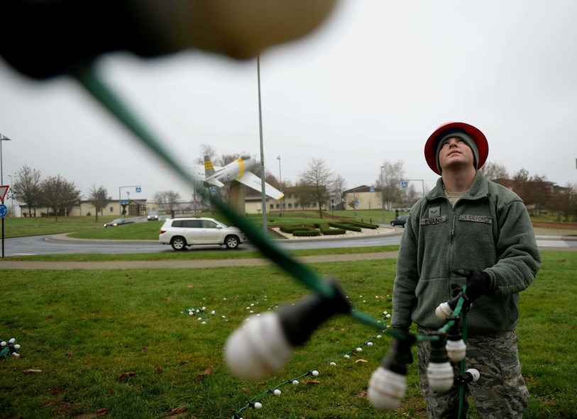 U.S. Air Force Senior Airman Zachery Evans, a 52nd Civil Engineer Squadron electrical systems journeyman and native of Clintwood, Va., decorates an evergreen tree at the Saber Circle on Spangdahlem Air Base, Germany, Dec. 2, 2014. The 52 CES ensured the tree's placement and decoration as per holiday tradition. (U.S Air Force photo by Airman 1st Class Timothy Kim/Released)