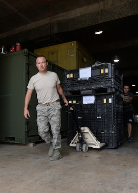 Master Sgt. Jesse Schwarztrauber, Operation Christmas Drop volunteer, moves crates containing donated items   Dec. 3, 2014, at Andersen Air Force Base, Guam. Operation Christmas Drop is an annual humanitarian airlift mission that began in 1952 and supplies more than 50 islands with boxes that contain donations such as non-perishable food items, clothing, medical supplies, tools, toys and other various items. (U.S. Air Force photo by Senior Airman Katrina M. Brisbin/Released.)
