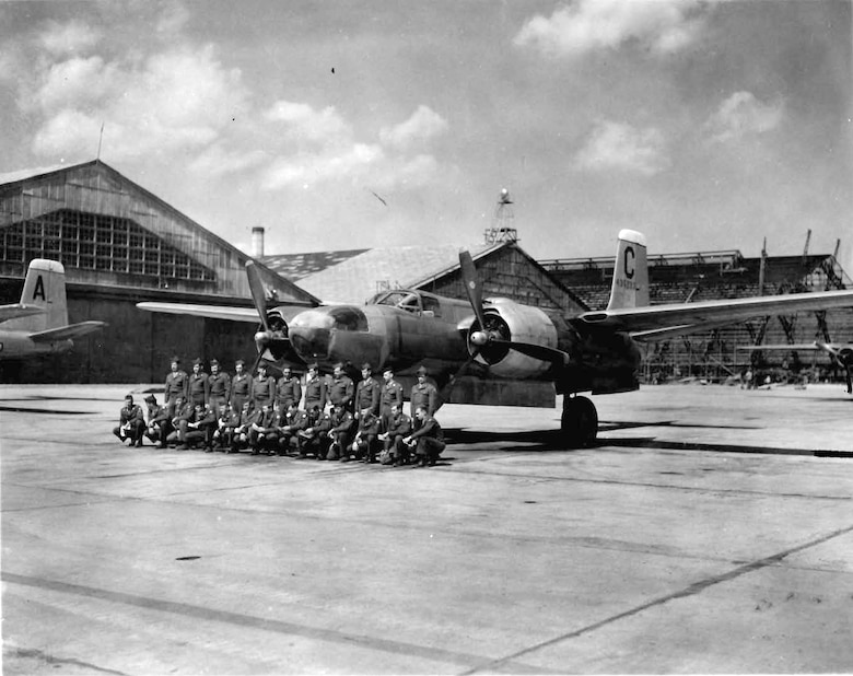 Students from Yokota Air Base's mechanics school pose in front of an A-26 Invader, March 1947. The hangar under construction in the background is still in use today.