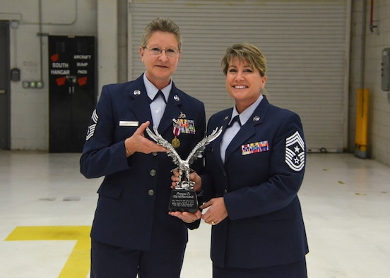 Chief Master Sgt. Connie Bacik, the command chief master sergeant of the 128th Air Refueling Wing, presents an award to Chief Master Sgt. Patti Winter-Schmidt during her retirement ceremony in an aircraft hangar here Dec. 7, 2014.  Winter-Schmidt served a 38-year career in the military and was the first female to be promoted to Chief Master Sgt. at the 128 ARW.  (U.S. Air National Guard photo by Master Sgt. Thomas J. Sobczyk/Released)