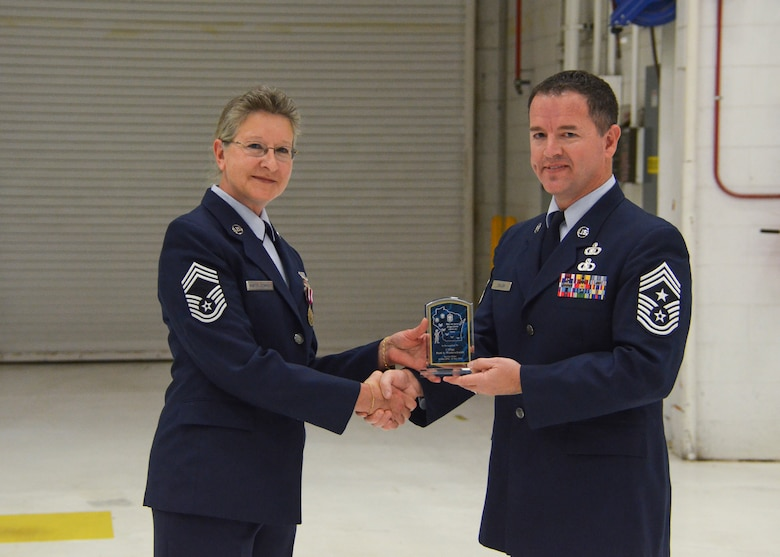 Chief Master Sgt. Greg Cullen, the command chief master sergeant of the State of Wisconsin, presents an award to Chief Master Sgt. Patti Winter-Schmidt during her retirement ceremony in an aircraft hangar here Dec. 7, 2014.  Winter-Schmidt served a 38-year career in the military and was the first female to be promoted to Chief Master Sgt. at the 128 ARW.  (U.S. Air National Guard photo by Master Sgt. Thomas J. Sobczyk/Released)