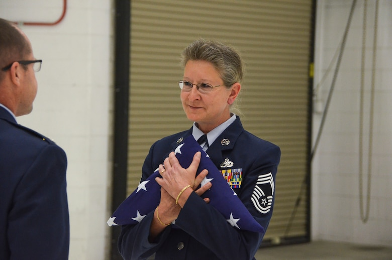 Chief Master Sgt. Patti Winter-Schmidt is bestowed a folded flag in honor of her military service during her retirement ceremony in an aircraft hangar here Dec. 7, 2014.  Winter-Schmidt served a 38-year career in the military and was the first female to be promoted to Chief Master Sgt. at the 128 ARW.  (U.S. Air National Guard photo by Master Sgt. Thomas J. Sobczyk/Released)