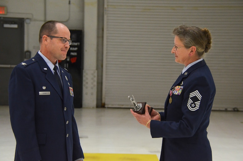 Col. James Locke, the vice wing commander of the 128th Air Refueling Wing, presents an award to Chief Master Sgt. Patti Winter-Schmidt during her retirement ceremony in an aircraft hangar here Dec. 7, 2014.  Winter-Schmidt served a 38-year career in the military and was the first female to be promoted to Chief Master Sgt. at the 128 ARW.  (U.S. Air National Guard photo by Master Sgt. Thomas J. Sobczyk/Released)