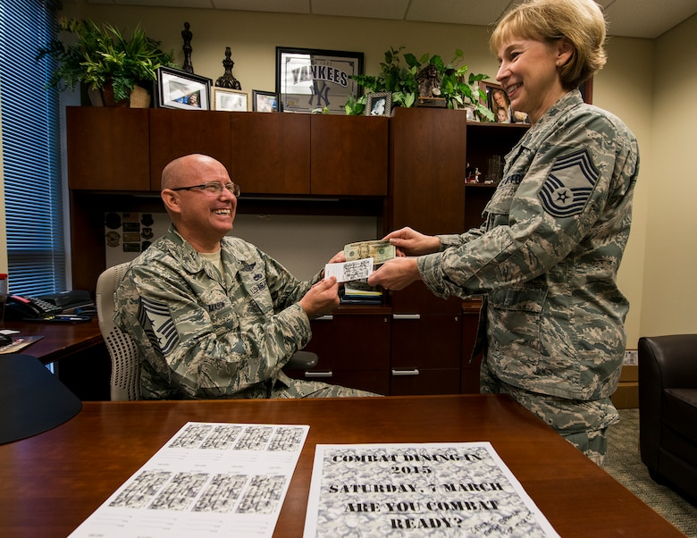 """Chief Master Sgt. Tom Mason, the 919th Special Operations Wing command chief, purchases the second combat dining-in ticket from Chief Master Sgt. Karilyn Graham, 919th Force Support Squadron Dec. 7 at Duke Field, Fla.  The wing will host its first """"dining-in"""" in nine years March 7 at 5 p.m. at the field behind the base dining facility.  Tickets are on sale now.  The event includes dinner, games and a guest speaker.  Ticket costs are:  E-1 – E-4 $7, E-5-E-6 $10 and E-7 and above $20.  The event is open to all military personnel assigned to the 919th SOW or the Air Force Special Operations Air Warfare Center working on Duke Field.  Contact any 919th SOW chief master sergeant to purchase tickets.   (U.S. Air Force photo/Tech. Sgt. Cheryl Foster)"""