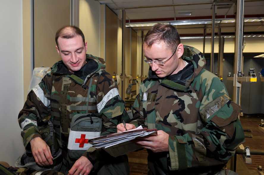Maj. Christopher Mahoney, 51st Medical Operations Squadron general surgeon, and Capt. Timothy Ewald, 51st MDOS mobile field surgical team orthopedic surgeon, review a chart to check the patients' vitals, x-rays and lab results after a simulated injury Dec. 6, 2014, at Osan Air Base, Republic of Korea. The exercise focuses on readiness, testing Osan's wartime procedures, and realistically looking at our ability to defend the base, execute operations and receive follow-on forces. (U.S. Air Force photo by Senior Airman David Owsianka)
