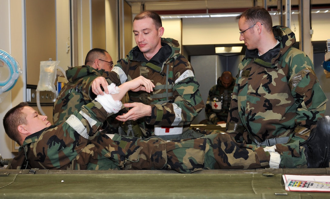 Maj. Christopher Mahoney, 51st Medical Operations Squadron general surgeon, evaluates a simulated forearm wound on Master Sgt. Donald Prothero, 51st Medical Group education and training flight chief, at Osan Air Base, Republic of Korea, Dec. 6, 2014. The disaster team performs operations on a variety of injuries such as gunshot and shrapnel wounds, burns, wounds from explosions or abdominal injuries. (U.S. Air Force photo by Senior Airman David Owsianka)