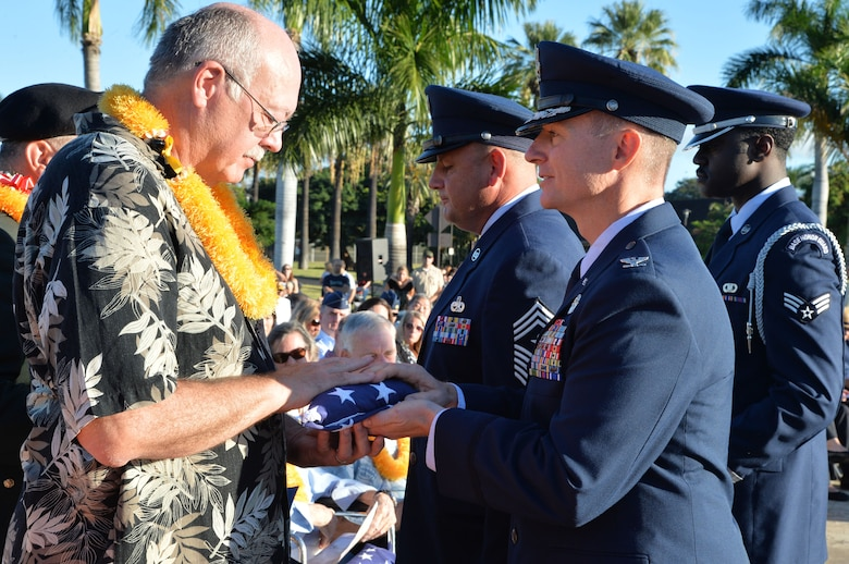 Col. Randy Huiss, right , presents an American flag to Thomas Shepherd during the 73rd Remembrance Ceremony at Joint Base Pearl Harbor-Hickam, Hawaii Dec. 7, 2014. Shepherd is the son of an Army Air Corpsman who survived the attacks on Hickam Field Dec. 7, 1941. More than 50 survivors and family members of survivors attended the ceremony, which honored the 189 Airmen who lost their lives in the attack. Huiss is the 15th Wing commander. (U.S. Air Force photo/Staff Sgt. Alexander Martinez)