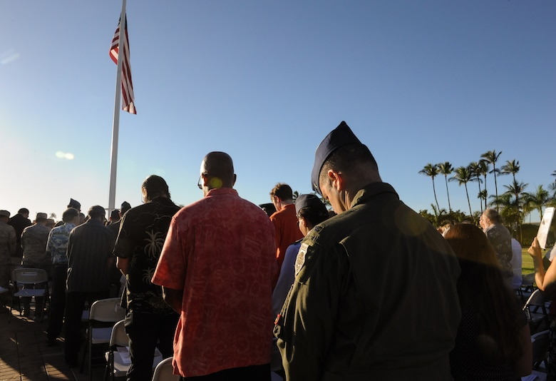 Attendees of the 73rd Remembrance Ceremony bow their heads during an invocation at Joint Base Pearl Harbor-Hickam, Hawaii Dec. 7, 2014. More than 50 survivors and family members of survivors attended the ceremony, which honored the 189 Airmen who lost their lives in the attack. (U.S. Air Force photo/2nd Lt. Kaitlin Daddona)