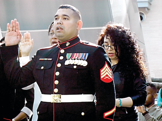 Sgt. Gustavo Antonio Arroliga-Lopez, a  Marine recruiter in Woodbridge and a native of Nicaragua, takes the Oath of Citizenship along with other new citizens during last month's Naturalization Ceremony at the National Museum of the Marine Corps last month.