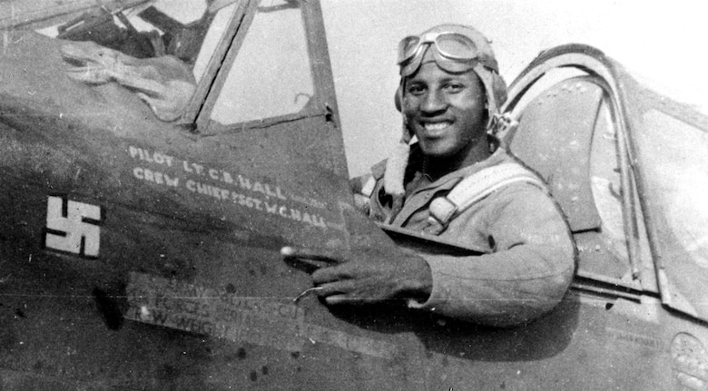 "While escorting B-25 Mitchell bombers over Sicily, 1st Lt. (later Maj.) Charles Hall scored the Tuskegee Airmen's first aerial victory. Seated in the cockpit of his P-40L Warhawk, Hall points to his freshly painted ""kill"" marking. (U.S. Air Force photo)"