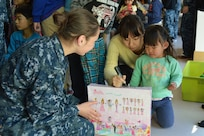 YOKOSUKA, Japan (Dec. 6, 2014) - Intelligence Specialist Seaman Amy Graham, from U.S. 7th Fleet flagship USS Blue Ridge (LCC 19), shares a gift with a local child from Shunkouen Spring Bright Garden Orphanage during a community relations (COMREL) event. Blue Ridge COMRELs strengthen relations promoting peace, stability and our commitment to our local communities. 141206-N-KG618-040