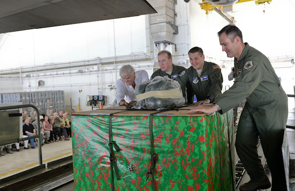 Leadership from Team Andersen, Yokota Air Base, Japan, the 515th Air Mobility Operations Wing, from Joint Base Pearl Harbor-Hickam, Hawaii, and Bruce Best, event guest speaker, push the first box onto a C-130 Hercules during the Push Ceremony, Dec. 9, 2014 at Andersen Air Force Base, Guam. The push Ceremony marks the beginning of the annual humanitarian airlift mission, Operation Christmas Drop, that supplies residents from more than 50 islands with boxes that contain donations to include non-perishable food items, clothing, medical supplies, tools, toys and other various items.  (U.S. Air Force photo by Staff Sgt. Robert Hicks/Released)