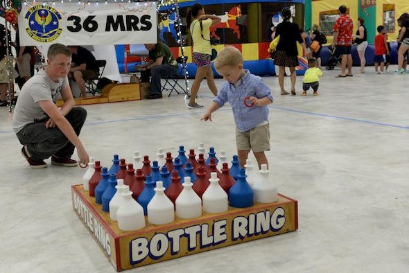 A Team Andersen family member plays bottle ring, Dec. 7, 2014, at Andersen Air Force Base, Guam.  Andersen held a holiday party that included games, a bounce house and a chance to take photos with Santa Claus.  (U.S. Air Force photo by Staff Sgt. Robert Hicks/Released)