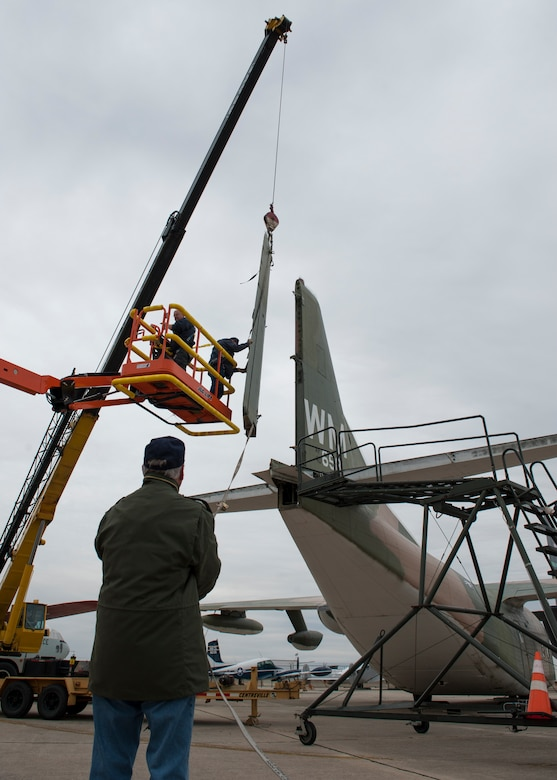Tom Galish, restoration volunteer, from the ground guides the detached rudder from a C-123K Provider cargo aircraft Nov. 13, 2014, at the Air Mobility Command Museum, on Dover Air Force Base Del. All of the museum's aircraft receive regular maintenance and restoration if needed to ensure their historic integrity. (U.S. Air Force photo/Airman 1st Class Zachary Cacicia)