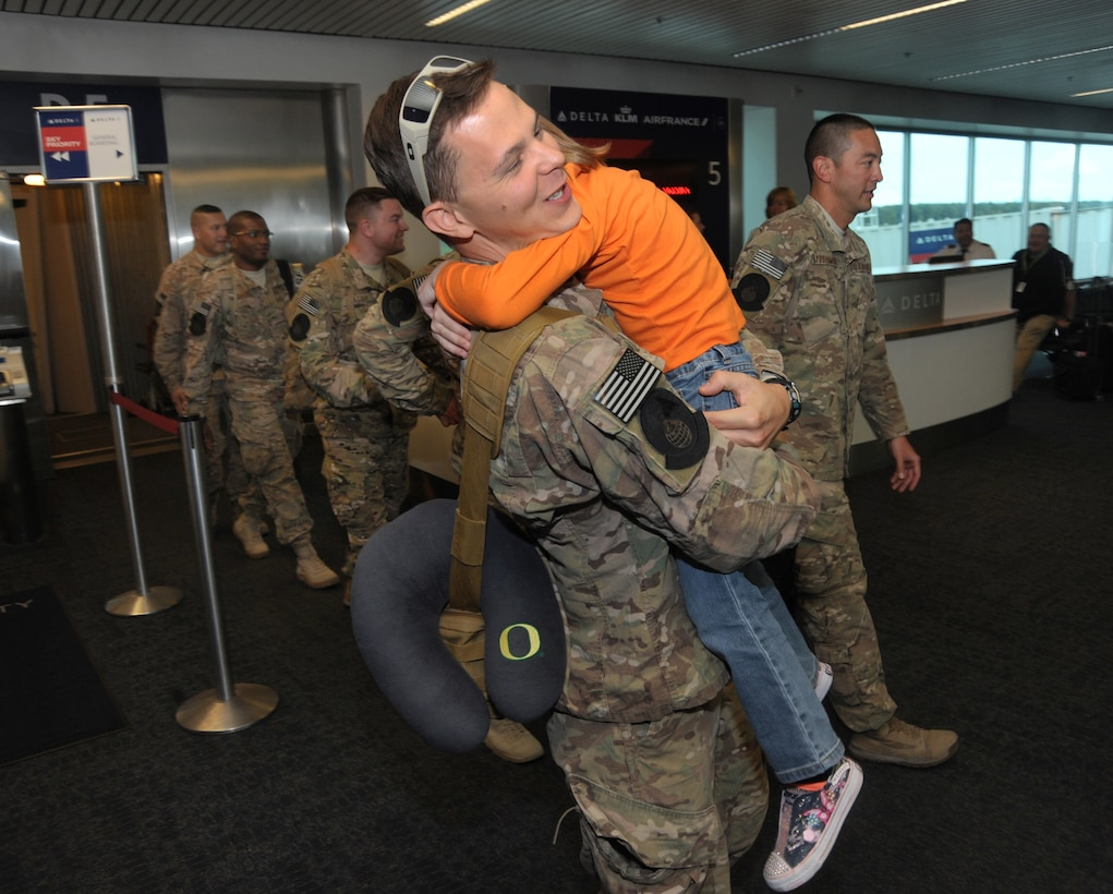 Staff Sgt. Jared Johnson, assigned to the 142nd Fighter Wing Security Forces Squadron is greeted by his daughter after returning home to Portland, Ore., from his OEF deployment, Oct. 31, 2014. (U.S. Air National Guard photo by Tech. Sgt. John Hughel, 142nd Fighter Wing Public Affairs/Released)