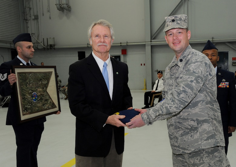 Oregon Governor John Kitzhaber receives the Oregon flag that was flown during deployment from Lt. Col. Jason Lay, 142nd Fighter Wing Civil Engineer Squadron Commander, during the formal Demobilization Ceremony at the Portland Air National Guard Base, Ore., Dec. 7, 2014. The Airmen recently returned from overseas deployment assignments to support Operation Enduring Freedom. (U.S. Air National Guard photo by Tech. Sgt. John Hughel, 142nd Fighter Wing Public Affairs/Released)