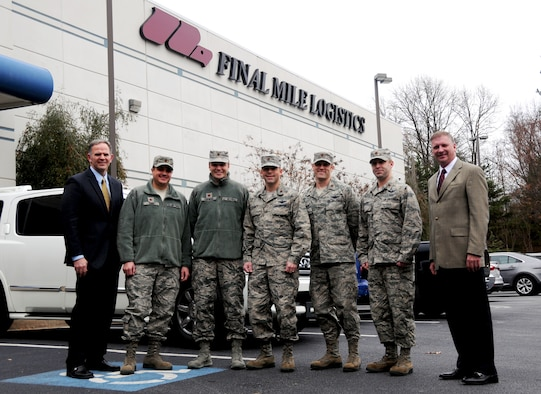Majors from Air Mobility Command pose for a photo with Colice Powell and Mark Gordon, both Final Mile Logistics, at FML in Atlanta, Ga., Dec. 8, 2014. Five majors from AMC came to the Atlanta area the week of Dec. 8 through 10 to speak to civilian business leaders as part of the Joint Mobility Fellowship Program. (U.S. Air Force photo by Senior Airman Daniel Phelps)