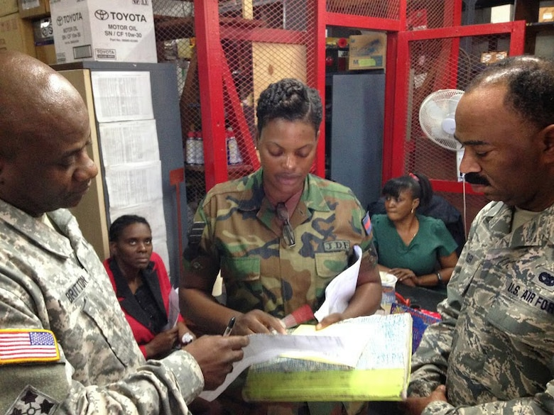 Jamaica Defence Force Sgt. Amelia Jones Ellis, technical store representative of the stores shop, explains her shop's mission to Chief Warrant Officer 2 Courtney Britton, D.C. National Guard team lead and maintenance manager (left), and Senior Airman Renardo Butler, vehicle mechanic of the 113th Wing, D.C. Air National Guard (right). As part of the State Partnership Program, the D.C. National Guard team of Air Force and Army wheeled vehicle maintenance experts are working alongside their JDF counterparts to exchange information and learn from each other. (U.S. Air National Guard photo by Capt. Renee Lee)
