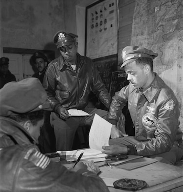 Wearing the jacket on display at the National Museum of the U.S. Air Force, Capt. (later Col.) Edward C. Gleed (right), the 332nd Fighter Group's operations officer and Lt. (later Lt. Col.) Woodrow W. Crockett (center) plan for a mission in March 1945. Note that Gleed later removed the 15th Air Force emblem from the jacket's left sleeve. (U.S. Air Force photo)