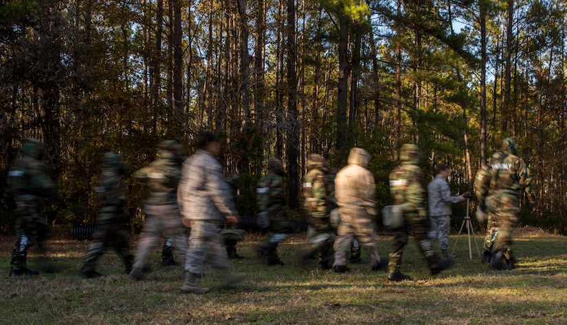 Chemical, biological, radiological, nuclear and high-yield explosives training instructors and students walk toward a liquid detection point to check for simulated contamination during a CBRNE refresher course Dec. 3, 2014, at Joint Base Charleston, S.C. After Air Force Basic military training, active-duty Airmen are required to go through CBRNE refresher training every two years. (U.S. Air Force photo/Senior Airman Marianique Santos)