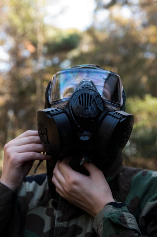 Airman 1st Class Dana Horn, 628th Air Base Wing command post controller, fastens the nape of her chemical suit during a chemical, biological, radiological, nuclear and high-yield explosives training course Dec. 3, 2014, at Joint Base Charleston, S.C. After Air Force Basic military training, active-duty Airmen are required to go through CBRNE refresher training every two years. (U.S. Air Force photo/Senior Airman Marianique Santos)